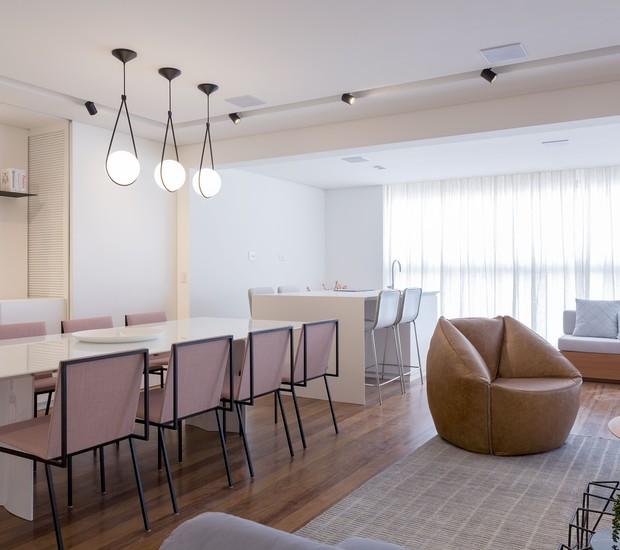 A mesa de jantar tem cadeiras da ,Ovo, mesma marca das banquetas sob a ilha. Os pendentes são da Decameron e, em destaque no living, a poltrona de couro vem do Estúdiobola (Foto: Marcelo Ribeiro/Divulgação)