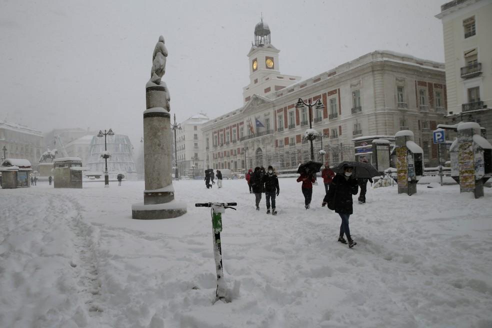Pessoas caminham ao cruzar a Praça do Sol durante uma forte nevasca em Madri, Espanha - 9 de janeiro de 2021 — Foto: Andrea Comas/AP Photo