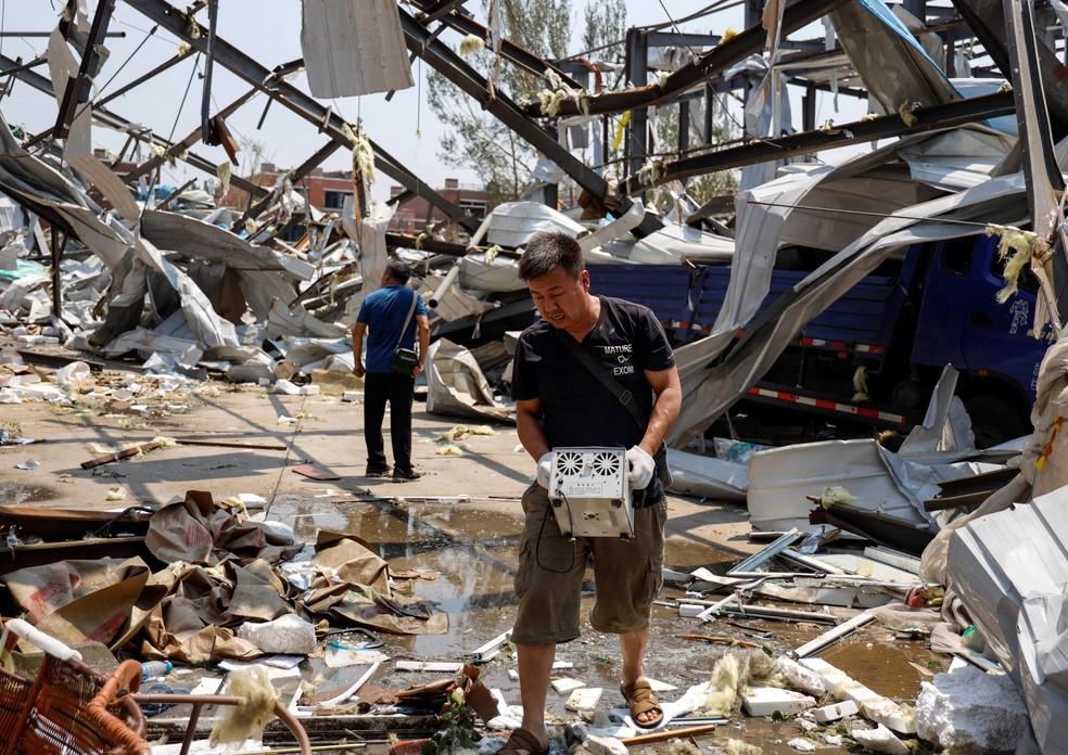 Pessoas buscam pertences em casas danificadas por um tornado em Kaiyuan, na província chinesa de Liaoning, nesta quinta-feira (4) — Foto: AFP