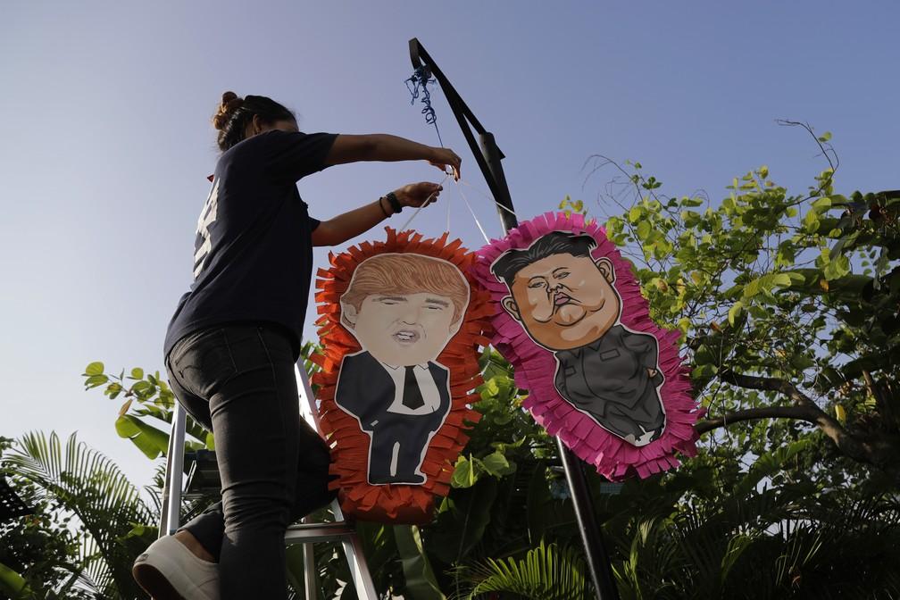 Funcionária de restaurante mexicano em Singapura pendura pinhatas de Trump e Kim dias antes da reunião histórica entre os líderes (Foto: Wong Maye-E/ AP Photo)
