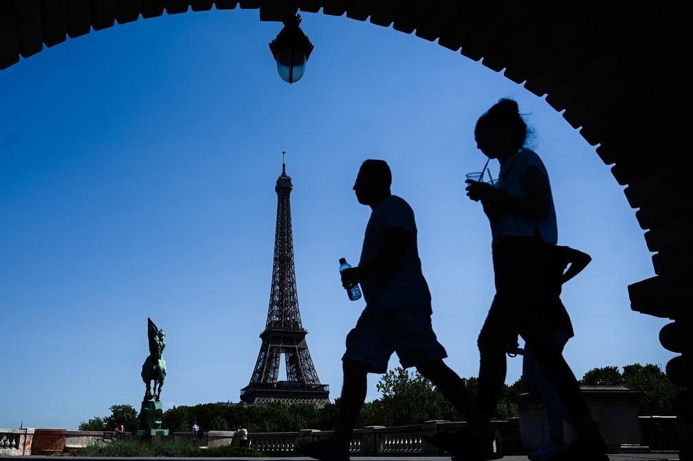 Um homem com uma garrafa d'água passa por uma mulher tomando uma bebida em uma ponte sobre o rio Sena, em frente à Torre Eiffel, em Paris, na França. Parisienses se preparam para o aumento da temperatura na capital francesa com a chegada de uma nova onda de calor no norte da Europa que pode bater recordes em vários países — Foto: Philippe Lopez/AFP