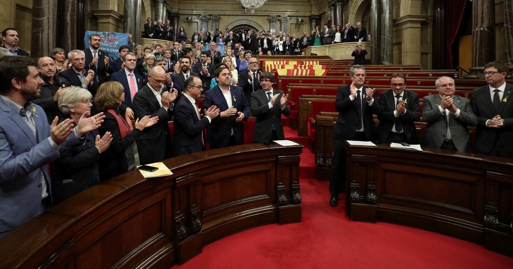 O presidente catalão Carles Puigdemont e deputados aplaudem aprovação de declaração da independência no Parlamento catalão em meio a assentos vazios dos deputados dos partidos PSC, Ciudadanos e PP (Foto: Reuters/Albert Gea)