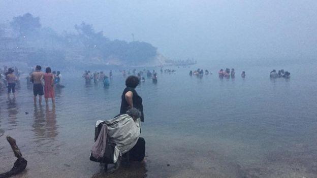Centenas de pessoas precisaram fugir do fogo pelo mar (Foto: Reuters via BBC)