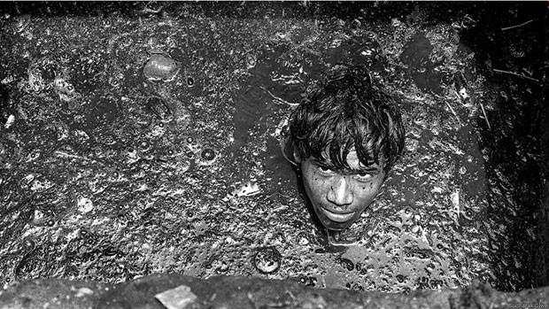 Essas pessoas muitas vezes têm de descer às galerias de drenagem de águas – algumas são tão profundas que poderiam acomodar um ônibus de dois andares. Depois de emergir, o trabalhador pode levar horas para se 'recuperar'. O trabalho não requer habilidades especiais, apenas um par de braços e pernas e a coragem de descer o que para muitos seria o 'inferno' (Foto: Sudharak Olwe)