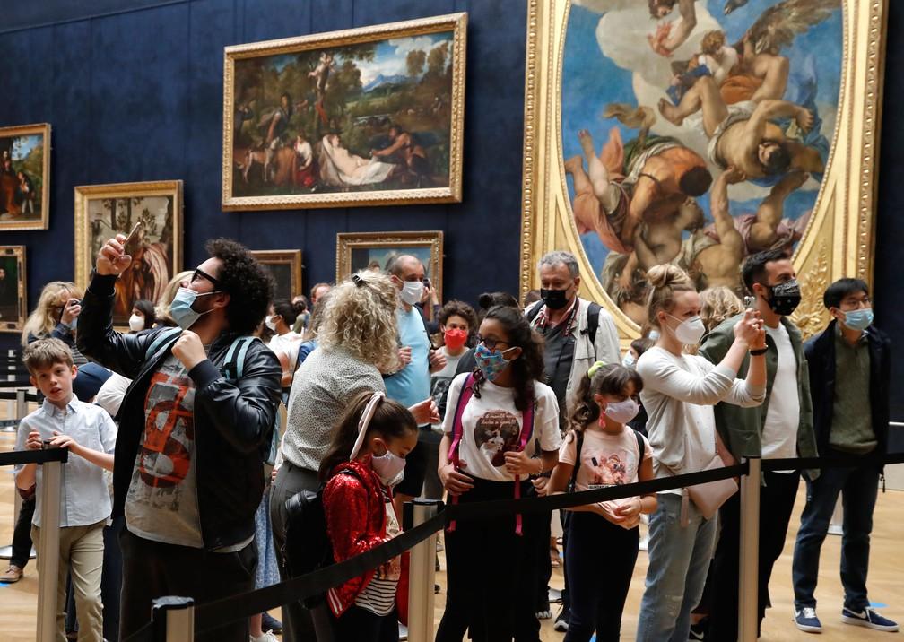 Visitantes com máscaras tiram fotos em frente à Mona Lisa, obra-prima de Leonardo da Vinci, no Lovre, nesta segunda-feira (6)  — Foto: Francois Guillot / AFP