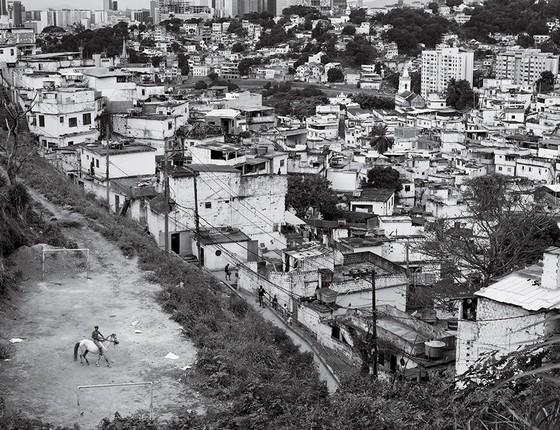 Um jovem monta um cavalo na Mineira Favela (favela) com a área do centro financeiro do distrito financeiro do Rio de Janeiro em segundo plano (Foto: João Pina)
