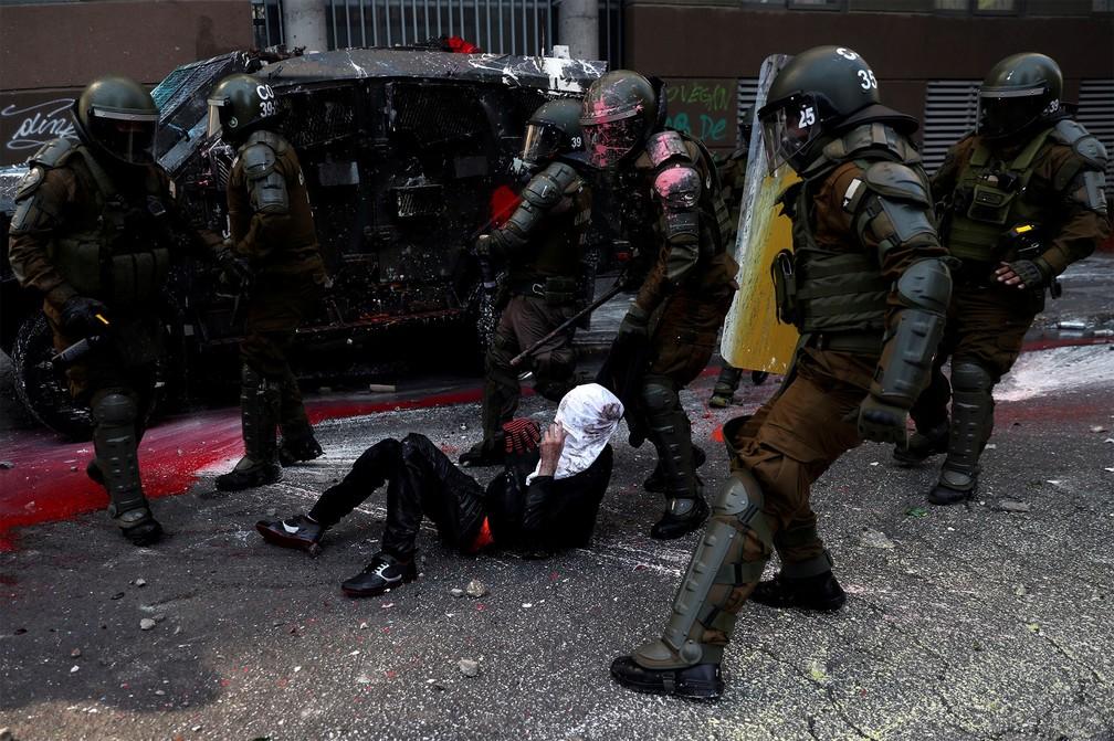 Policiais detêm um manifestante durante confronto em Santiago neste domingo (18) — Foto: Ivan Alvarado/Reuters