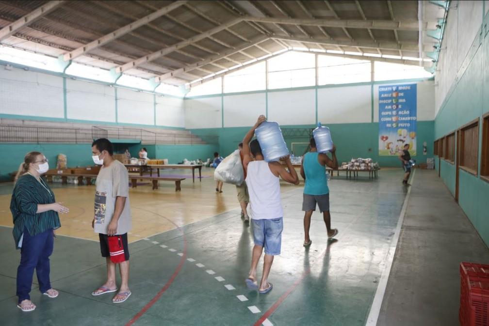 Manhã de sexta (18): homens carregam galões de água em abrigo na Escola Tancredo Neves em Presidente Getúlio — Foto: Patrick Rodrigues/NSC