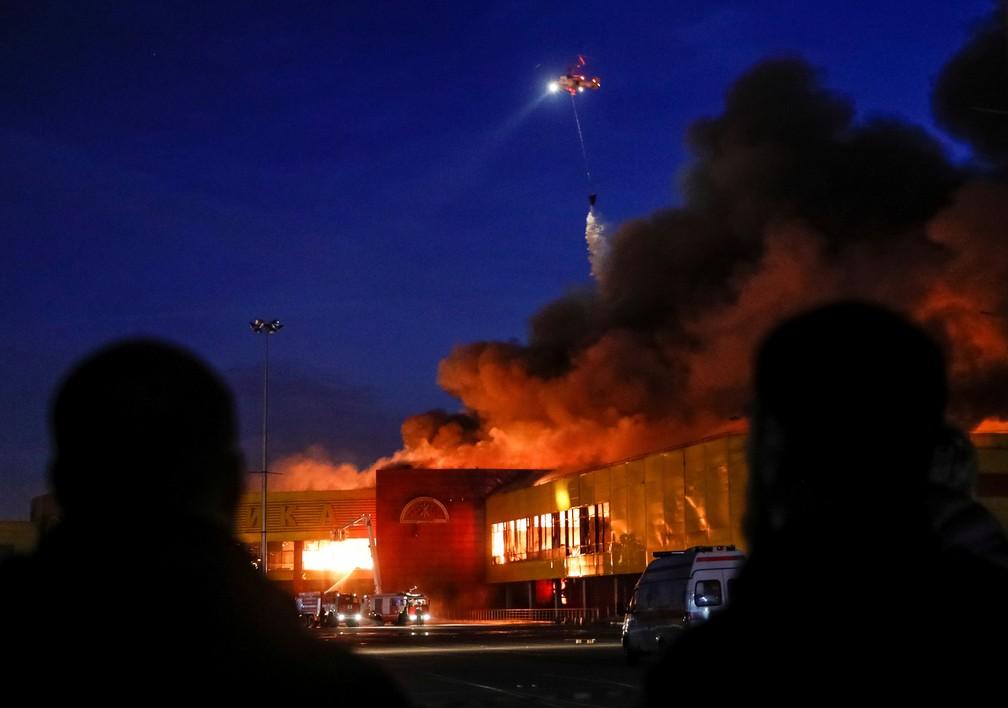 Pessoas observam helicóptero jogando água contra shopping incendiado em Moscou (Foto: REUTERS/Maxim Shemetov)
