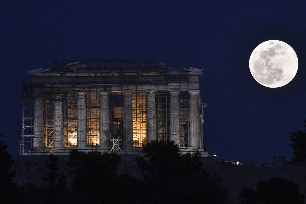 A Superlua se ergue ao lado do templo do Parthenon em Acrópole, na Grécia, nesta terça-feira (19). — Foto: Louisa Gouliamaki/AFP