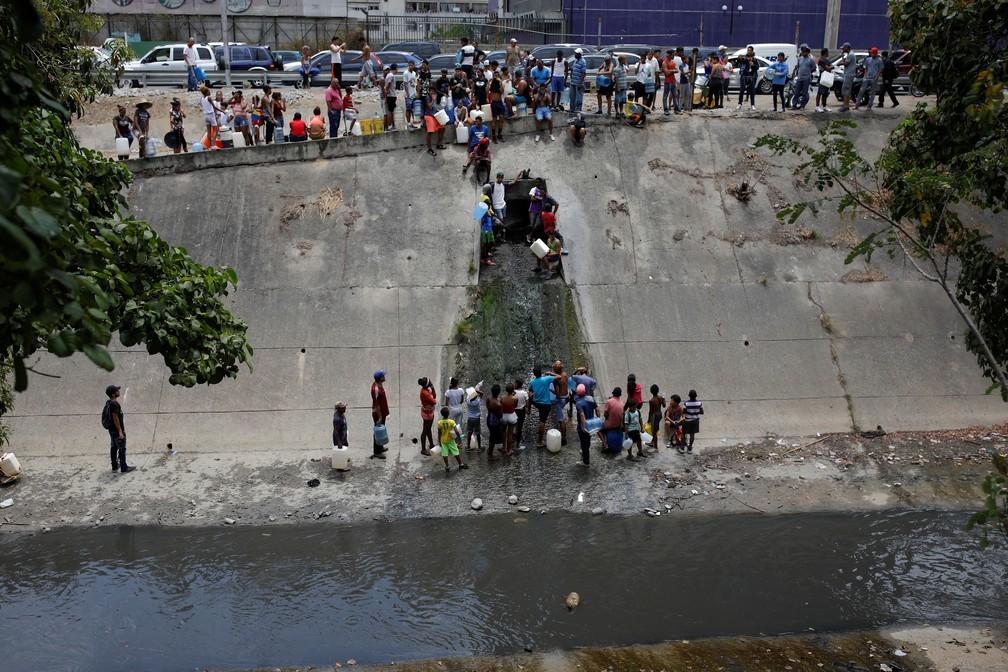 Moradores captam água de saída de esgoto que corre para o Rio Guaire, um dos mais poluídos de caracas — Foto: Reuters/Carlos Garcia Rawlins