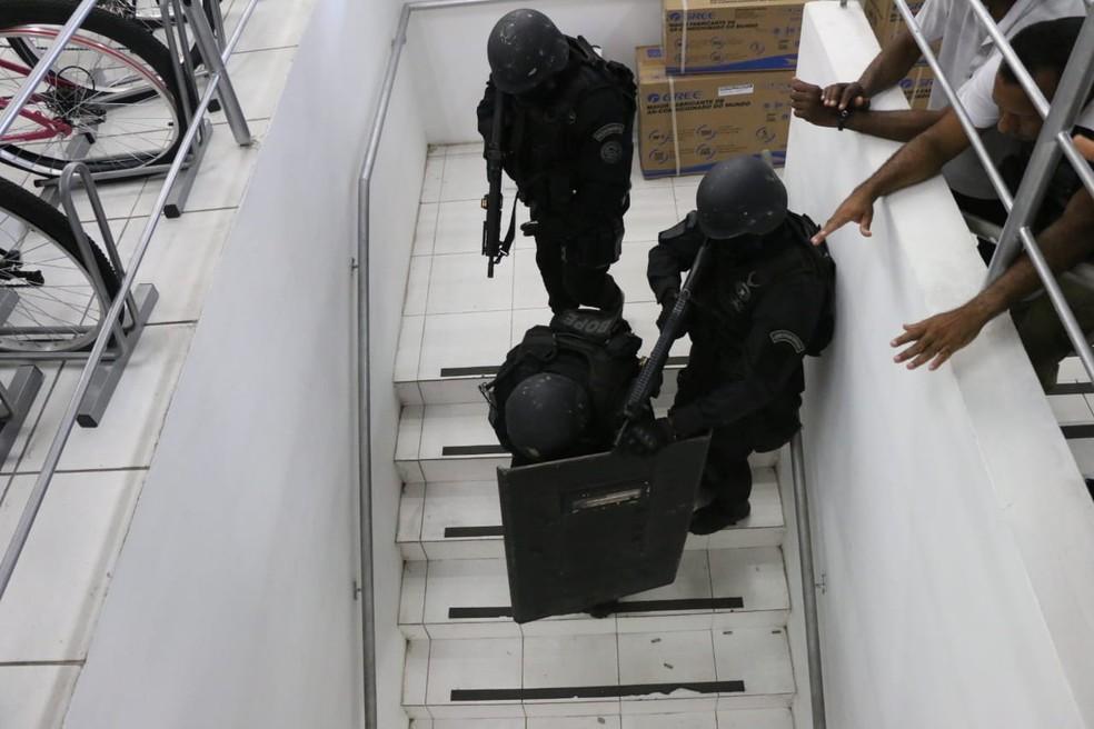 Policiais recolhem arma usada por um dos suspeitos de invadir loja em Lauro de Freitas, Bahia — Foto: Alberto Maraux/ SSP-BA