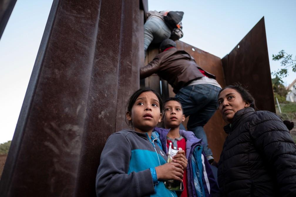 Migrantes da América Central sobem a cerca da fronteira México-EUA enquanto outros hesitam. Registro foi feito na quarta-feira (12)  — Foto: Guillermo Arias / AFP