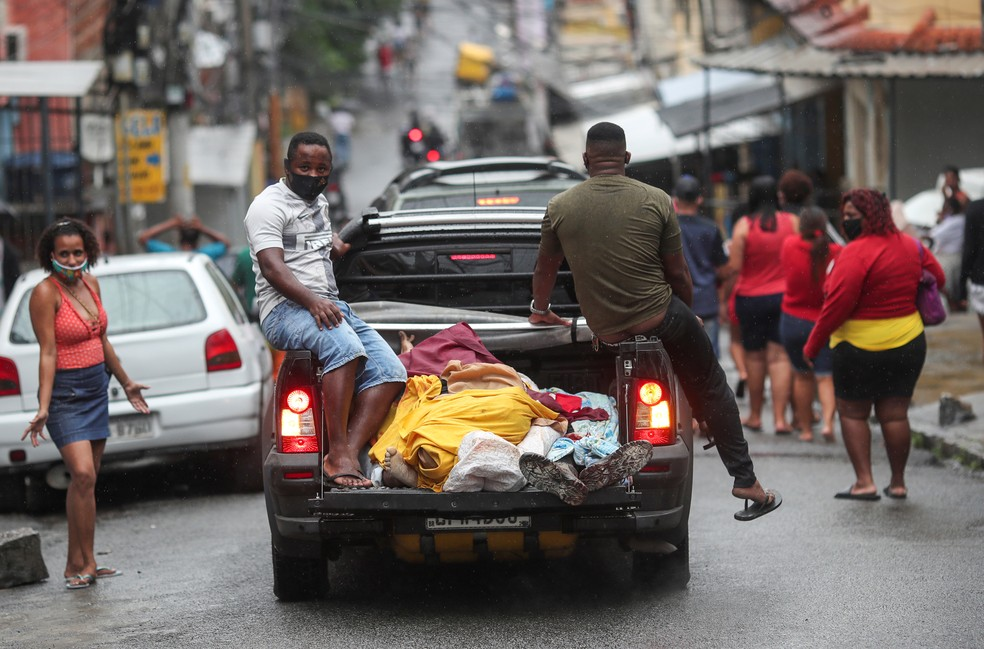 Moradores do Complexo do Alemão transportam corpos após operação policial, no Rio de Janeiro — Foto: Ricardo Moraes/Reuters