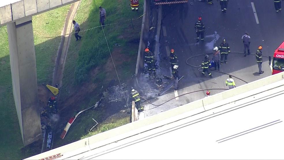 Bombeiros observam o que sobrou do helicóptero — Foto: TV Globo/Reprodução