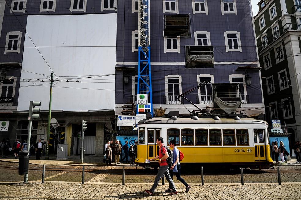 -  Turistas passam em frente a um prédio em reforma em Lisboa, Portugal  Foto: Patricia de Melo Moreira/AFP