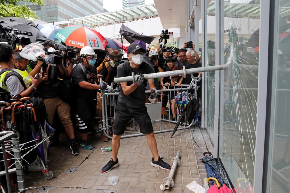 Manifestante tenta estourar porta de vidro do Parlamento de Hong Kong — Foto: REUTERS/Tyrone Siu
