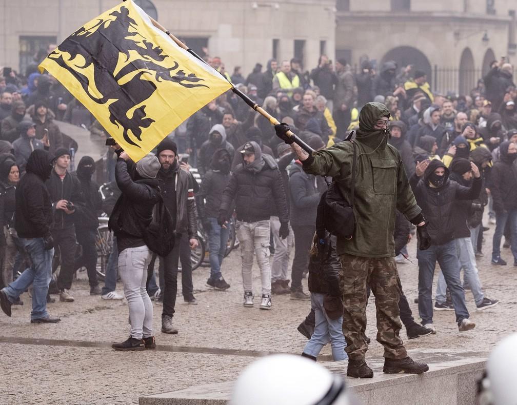 Um manifestante agita uma bandeira flamenca contra a polícia durante uma manifestação anti-imigrantes fora da sede da União Europeia, em Bruxelas. — Foto: Associated Press
