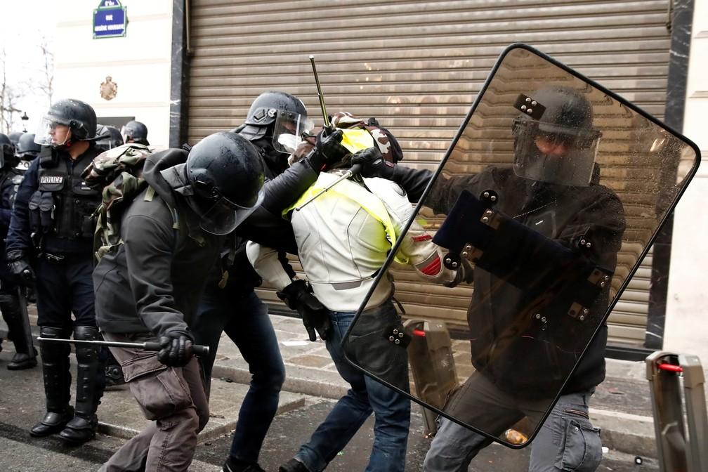 Policiais prendem manifestante durante protestos na região da Champs Elysees — Foto: Christian Hartmann/Reuters