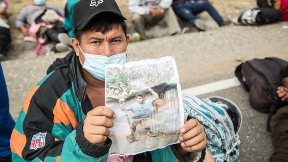 Wilmer, um hondurenho da caravana de migrantes que atravessa a Guatemala, mostra uma foto de sua casa destruída pela tempestade Eta, motivo pelo qual decidiu ir para os EUA — Foto: EPA/BBC