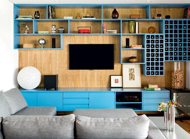 A designer de interiores Magda Marconi criou uma estante com nichos de tamanhos variados e com acabamento de laca azul, fixados no painel de freijó sarrafeada, onde a televisão foi fixada. A execução é da Japy Marcenaria (Foto: Edu Castello e Maíra Acayaba/Editora Globo)