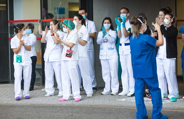 MADRID, SPAIN – APRIL 05: Sanitary personal of Villalba General Hospital are seen at the Emergency entrance while local police, civil guard and firefighters applaud them on April 05, 2020 in Madrid, Spain. Spain ordered all non-essential workers to stay h (Foto: Getty Images)