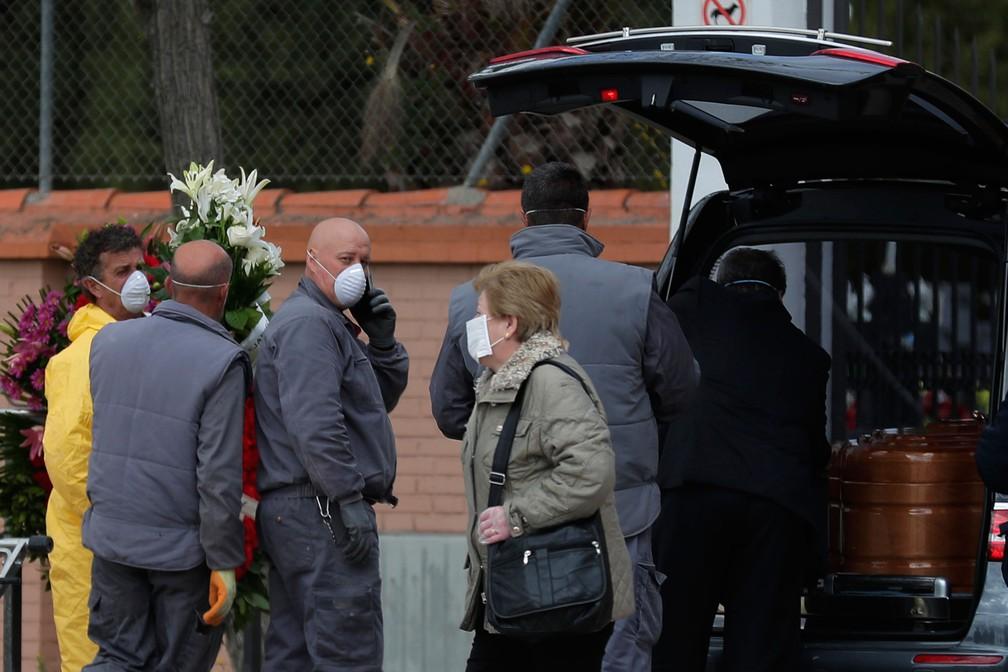 Agentes funerários carregam o caixão com vítima de Covid-19, no cemitério em Leganes, na Espanha, na terça-feira (24) — Foto:  Manu Fernandez / AP