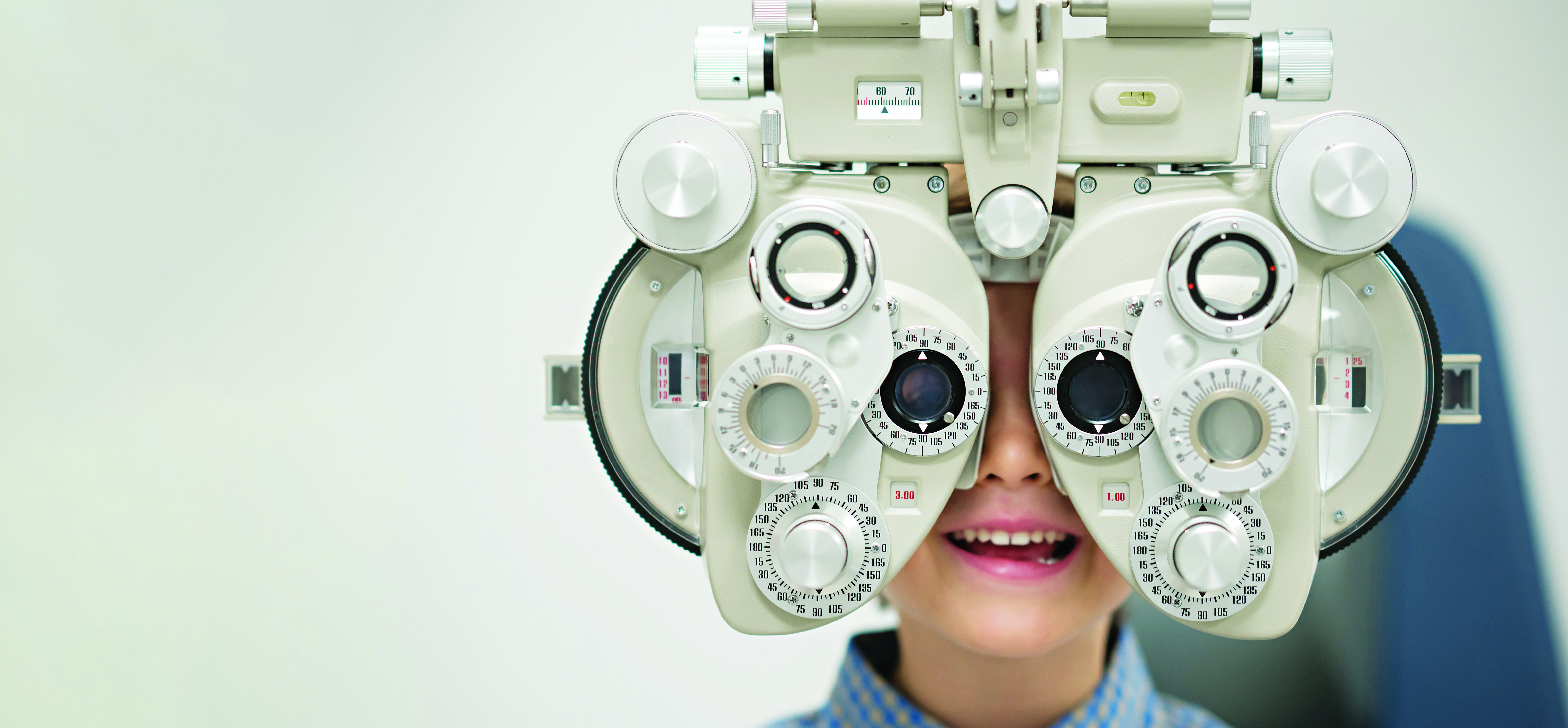 Young patient getting an eye exam at the optician on the phoropter â?? healthcare and medicine concepts (Foto: Getty Images)