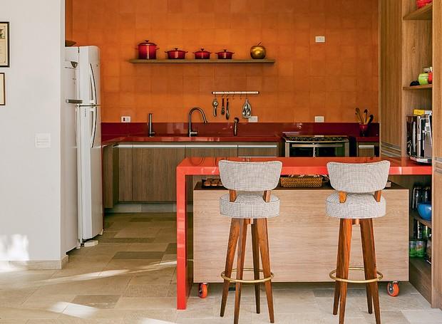 A cozinha do projeto do escritório Arkitito é praticamente monocromática, com ladrilho hidráulico, bancadas e panelas laranjas (Foto: Edu Castello/Casa e Jardim)