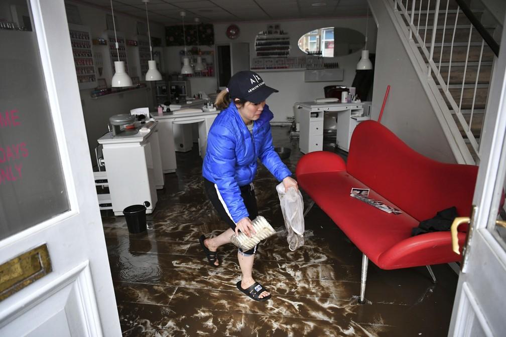 Mulher tenta limpar salão de beleza inundado pela tempestade Dennis em Pontypridd, no País de Gales, neste domingo (16) — Foto: Ben Birchall/PA via AP