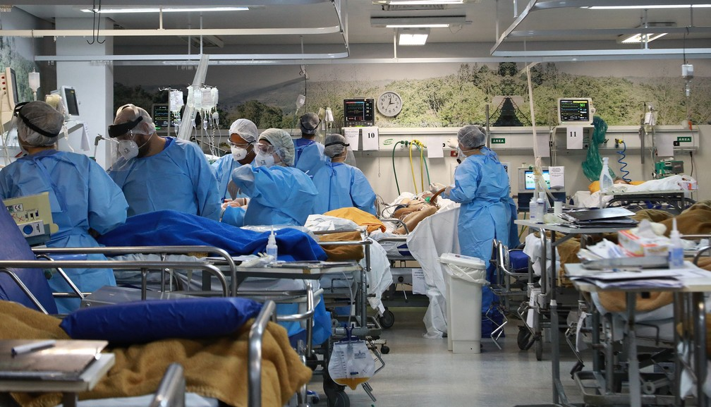 Profissionais  de saúde cuidam de pacientes com Covid-19 em uma UTI de Porto Alegre, no dia 11 de março. — Foto: Silvio Avila/AFP