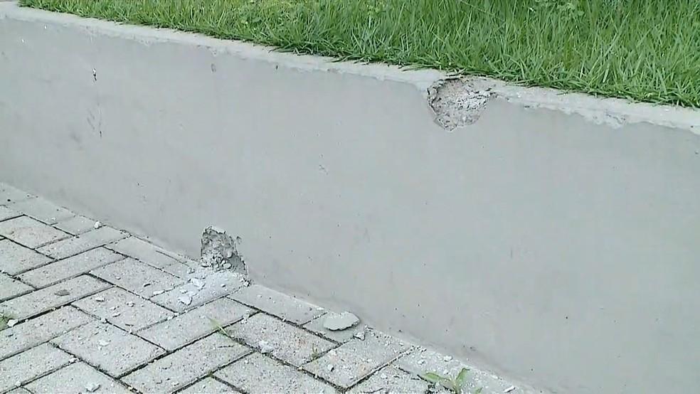 Marcas de tiros deixadas em muro nas imediações do banco invadido por criminosos em Criciúma — Foto: Reprodução/ NSC TV