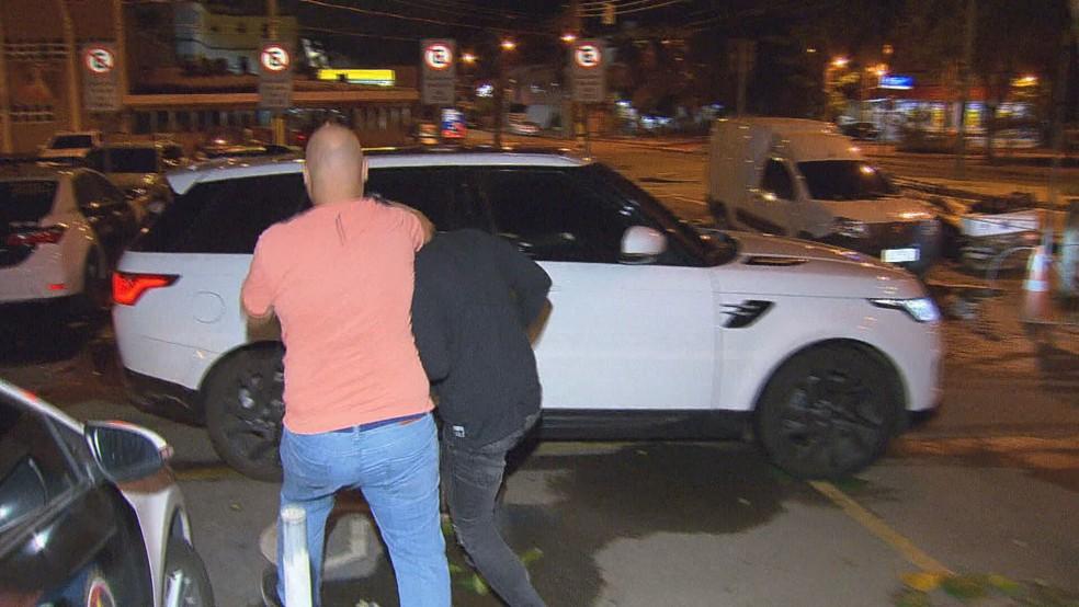 Bruno Henrique é levado para o próprio carro após deixar a delegacia — Foto: Reprodução/TV Globo