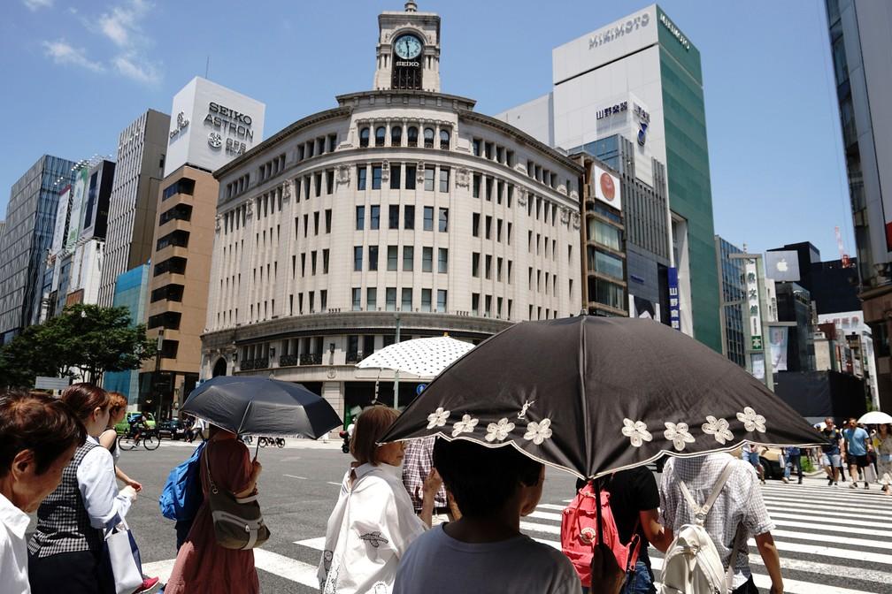 Pessoas caminham sob sol intenso na sexta-feira (20) em Tóquio, no Japão  (Foto: Eugene Hoshiko/AP)