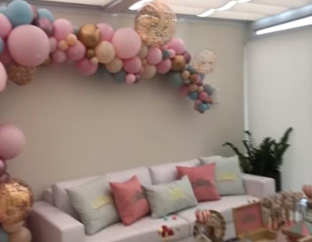 O sofá recebeu almofadas e personalizadas. Na parede um arco desconstruído de balões (Foto: Reprodução Youtube)