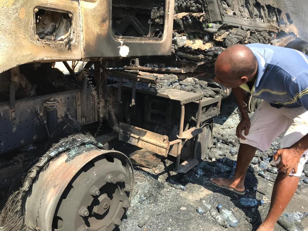 Motorista olha carreta destruída por incêndio — Foto: Abmael Milhomem/Divulgação