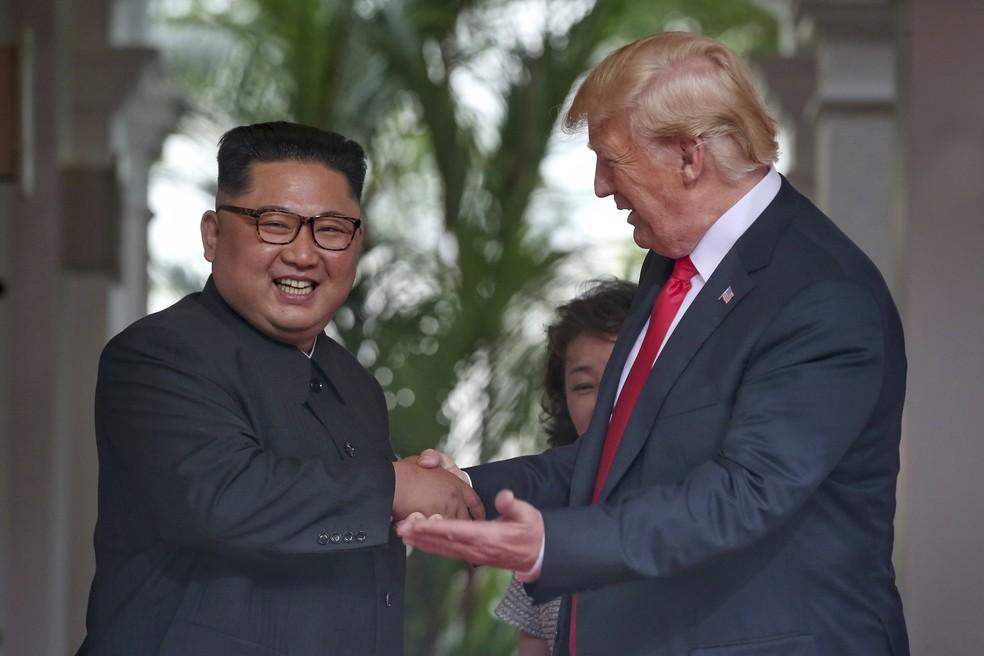 Kim Jong-un e Donald Trump sorriem ao se cumprimentar durante reunião em Singapura — Foto: Kevin Lim/The Straits Times via AP