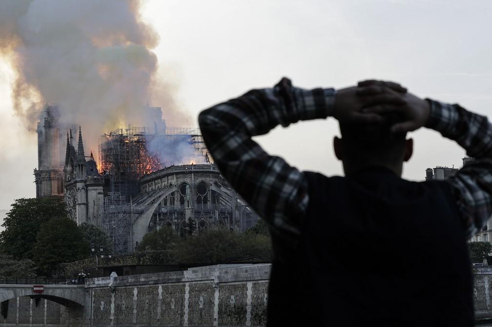 Homem leva as mãos à cabeça enquanto observa o incêndio que consome a Catedral de Notre-Dame, em Paris — Foto: Geoffroy Van Der Hasselt/AFP