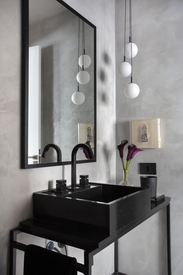 Banheiro com cuba de apoio preta sob estrutura de ferro preta, paredes revestidas de cimento queimado, espelho quadrado com moldura preta
