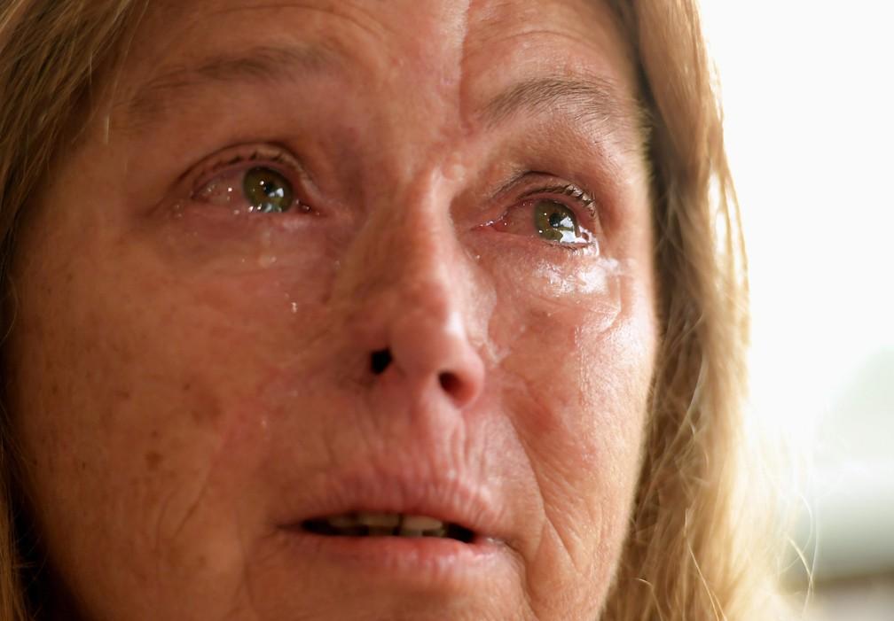 Sheryl Turner, moradora que teve dificuldade de evacuar sua casa porque estava sem gasolina, chora ao falar do tamanho dos incêndios enquanto toma um café em um centro de evacuação em Bomaderry, na Austrália — Foto: Tracey Nearmy/Reuters