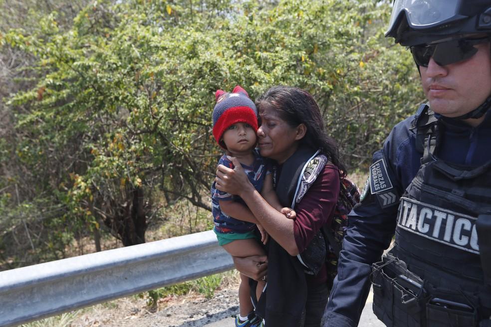 Policial escolta mãe e filho migrantes da América Central detidos enquanto atravessavam o México — Foto: Moisés Castillo/AP Photo