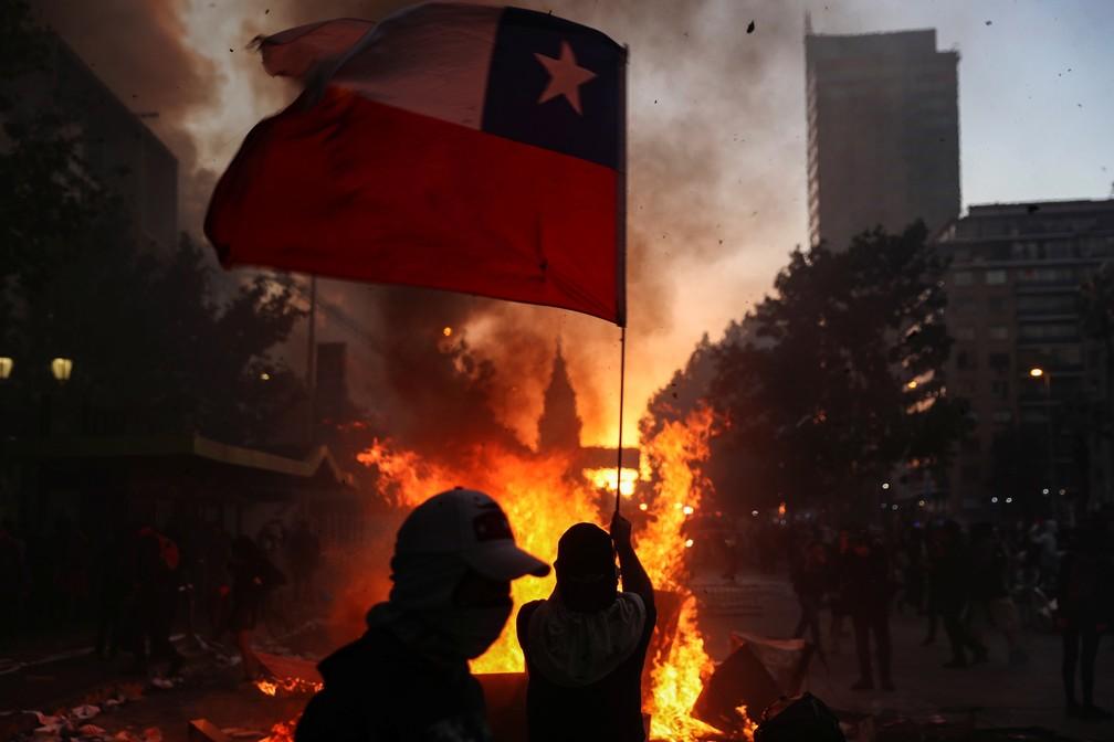 Manifestante carrega bandeira chilena em frente a barricada no centro de Santiago, no Chile, nesta segunda-feira (28) — Foto: Edgard Garrido/Reuters