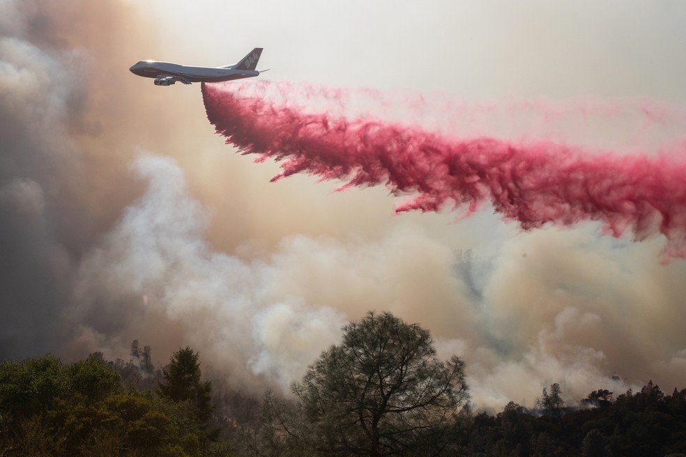 Aeronave joga produto para apagar incêndio no Glass Park, na Califórnia, neste domingo (27) — Foto: Adrees Latif/Reuters