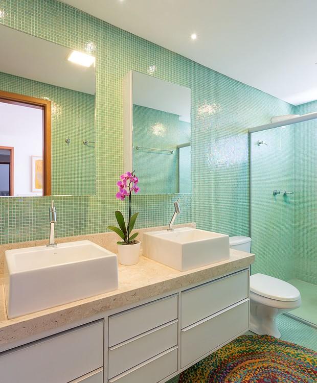O banheiro da suíte é um dos ambientes transformado pelo efeito dos blocos de cor, graças às pastilhas de vidro verde presentes no piso e nas paredes (Foto: Paulo Rezende)
