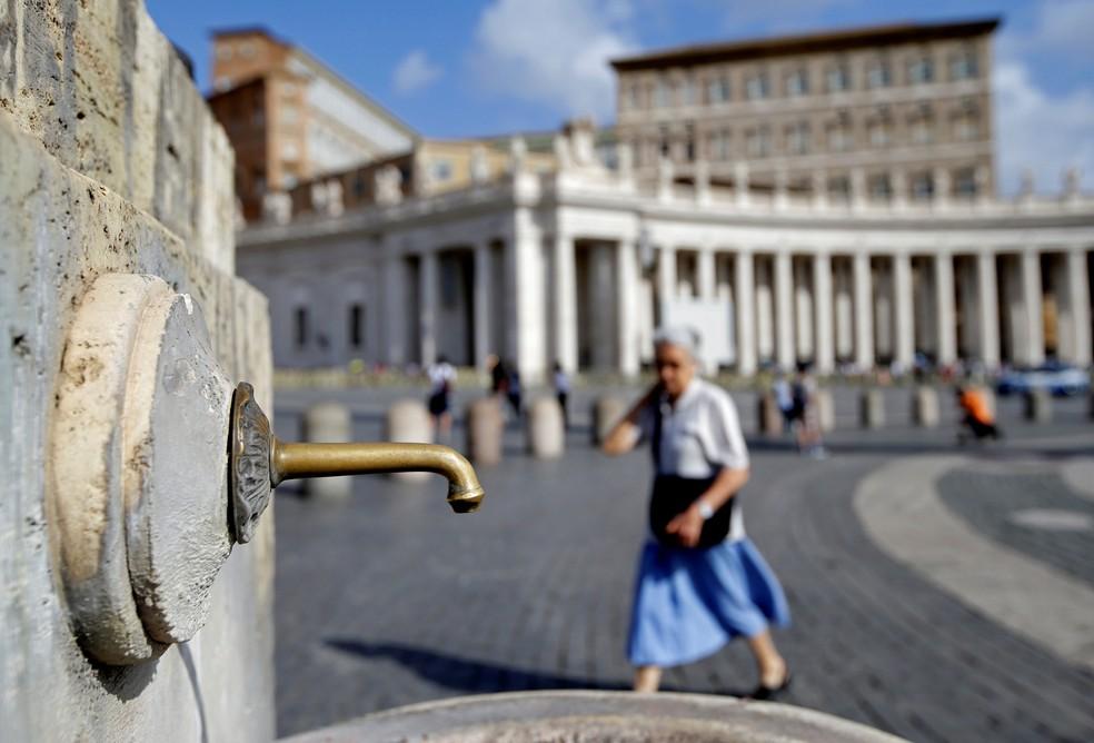 Mulher caminha perto de fonte na Praça São Pedro no Vaticano, nesta terça-feira (25)  (Foto: Max Rossi/ Reuters)