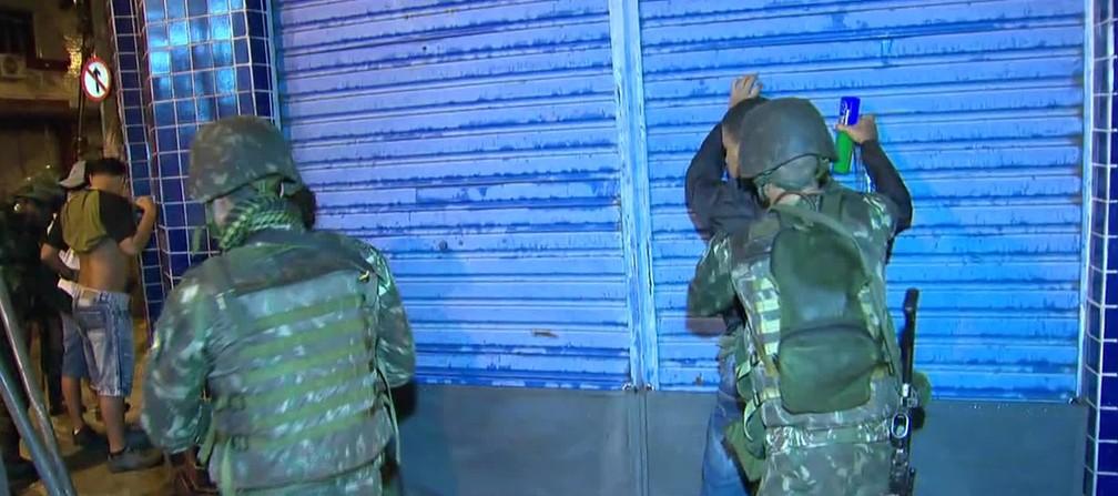 Agentes das forças federais fazem revistas nos pontos de bloqueios da cidade. (Foto: Reprodução/ TV Globo)