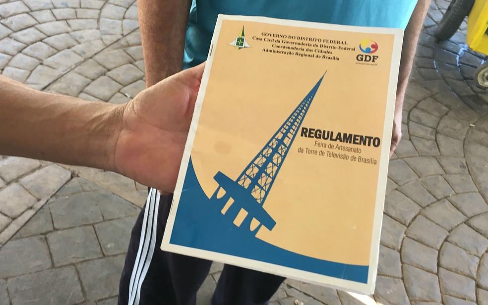 Artesão mostra Regulamento da Feira da Torre de Brasília (Foto: Luiza Garonce/G1)