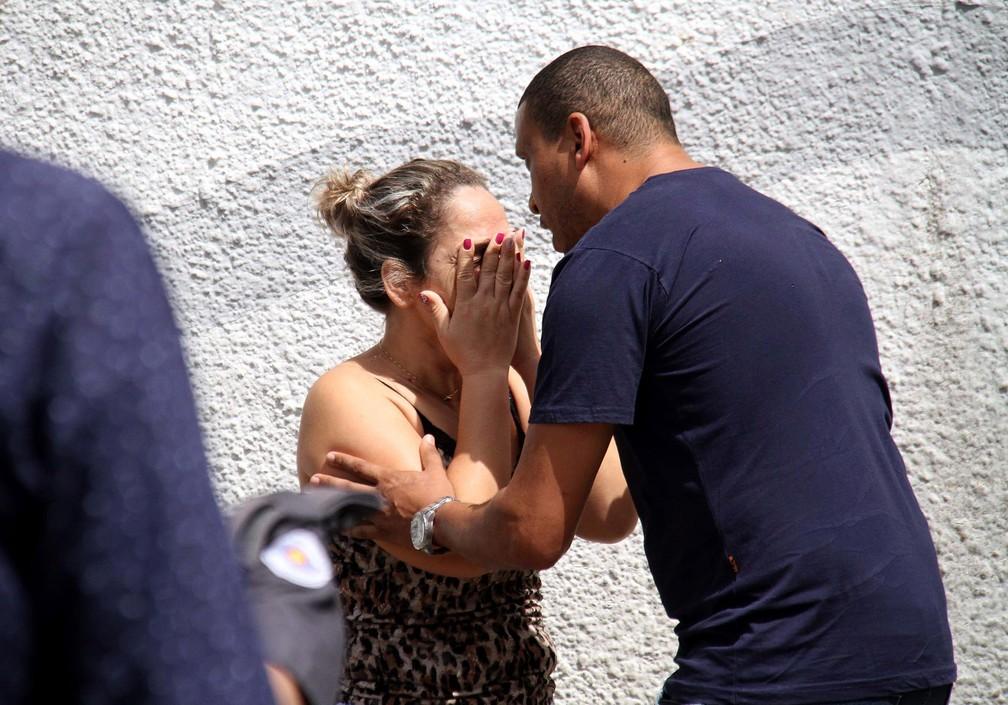 Um homem tenta acalmar uma mulher na entrada da Escola Estadual Raul Brasil em Suzano, na Grande São Paulo. Dois criminosos encapuzados mataram oito pessoas no local e cometeram suicídio em seguida — Foto: Maurício Sumiya/Futura Press via AP