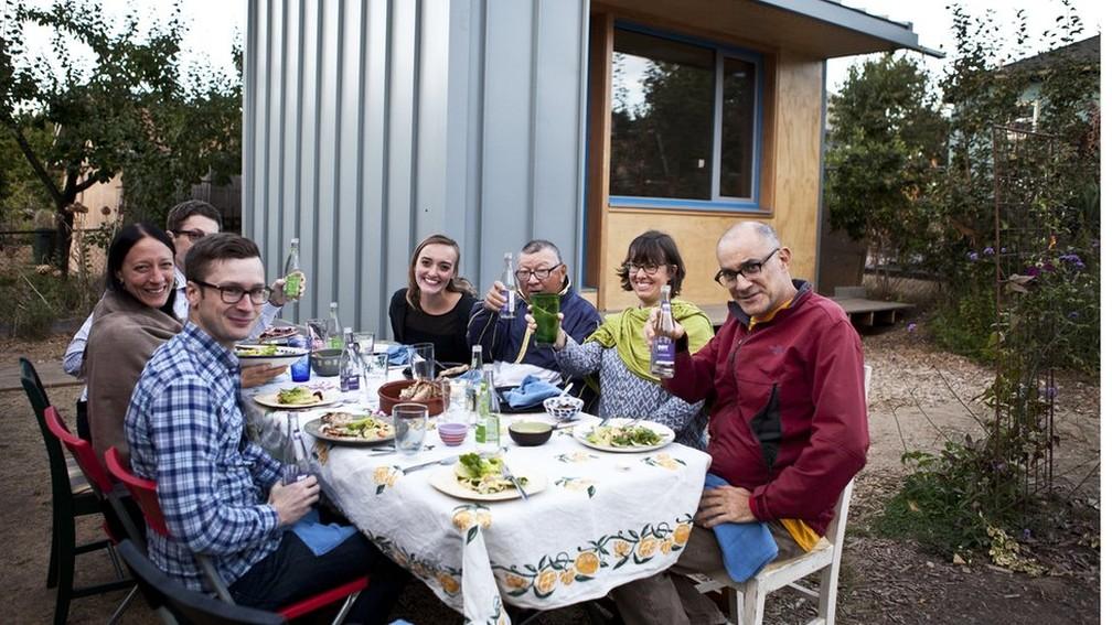 6 bobby de jaqueta azul e membros da vizinhanca em frente a primeira microcasa construida pelo projeto - Em meio à crise de moradia, cidades dos EUA incentivam proprietários a abrigar sem-teto no quintal de casa