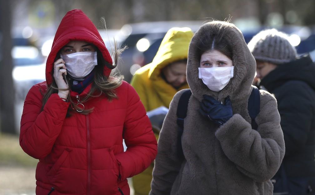 Mulheres usam máscaras contra o novo coronavírus em Minsk, Bielorrússia, nesta sexta-feira (28). — Foto: Sergei Grits/AP